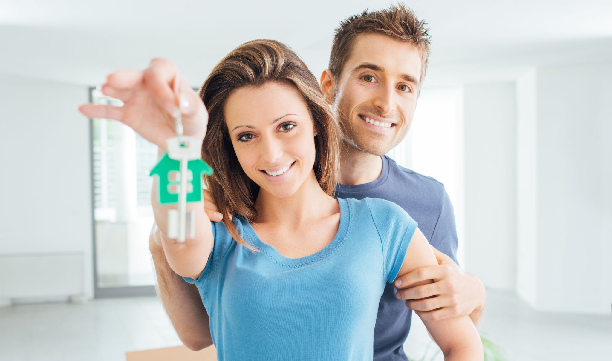 Young smiling couple holding their new house keys real estate and relocation concept